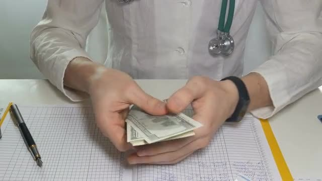 Doctor Counting Money In Hospital: Stock Video