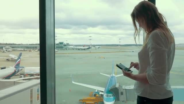 Woman With Smartphone At Airport: Stock Video
