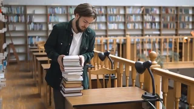Man With Books In Library: Stock Video