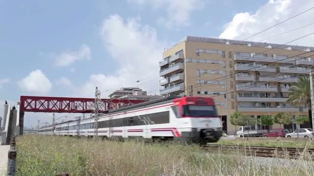 Commuter Train Passing Under Footbridge: Stock Video