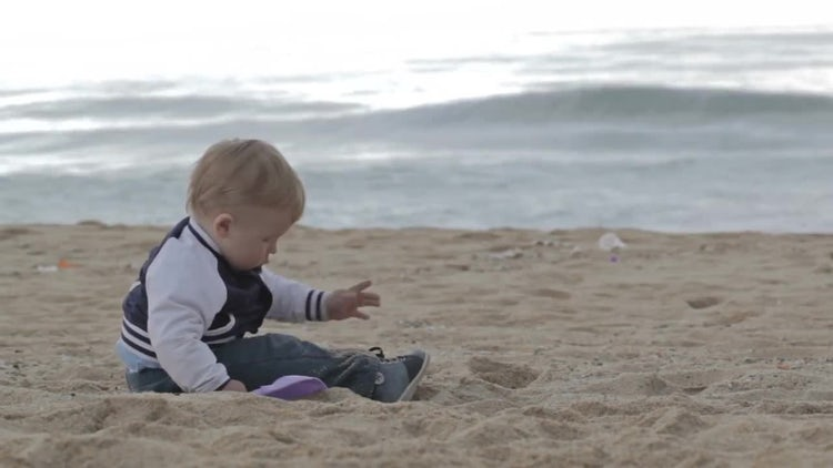 Boy Playing With Beach Sand: Stock Video