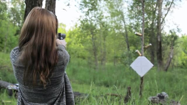 Girl Shoots Gun At Targets: Stock Video