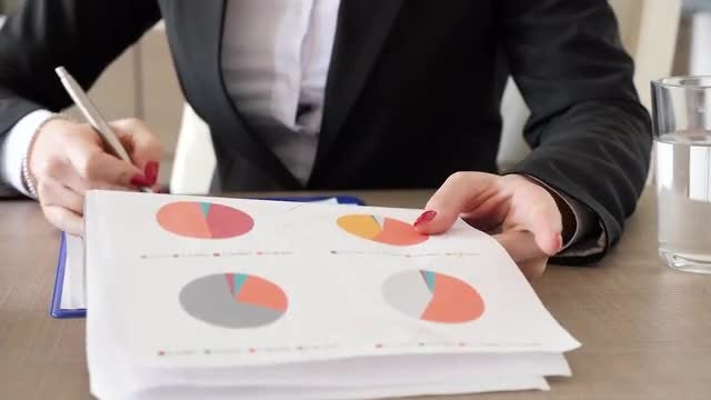 Businesswoman Going Through Business Charts : Stock Video