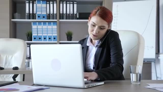 Businesswoman Typing While Taking Call: Stock Video