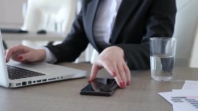 Businesswoman Taking Call While Typing: Stock Video