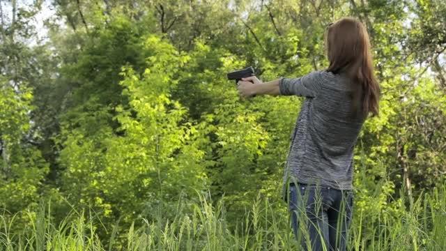Girl Shoots Gun Outdoors: Stock Video