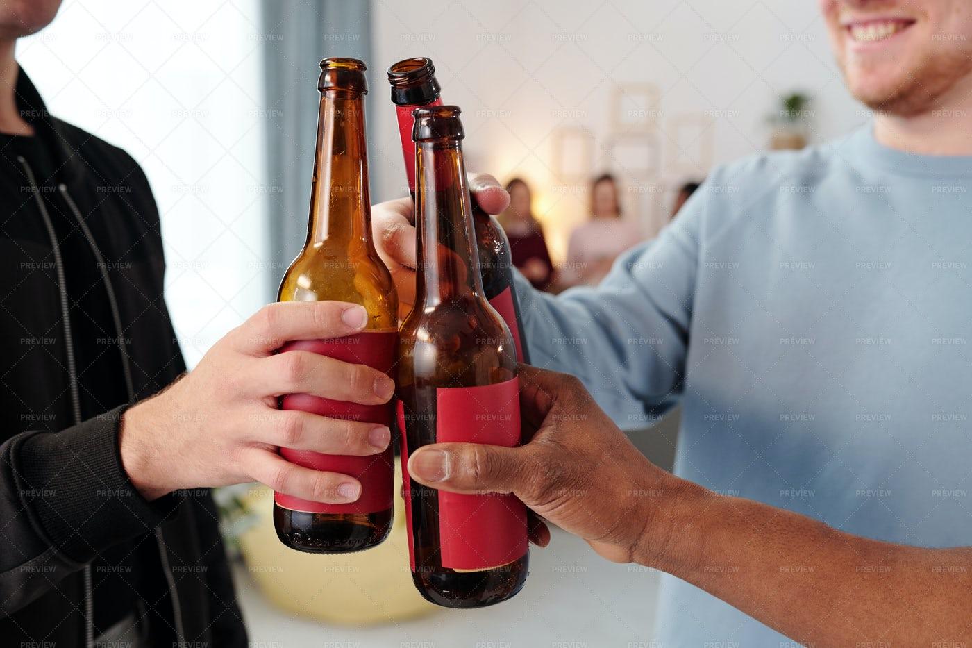 Hands Of Men Clinking Beer Bottles: Stock Photos