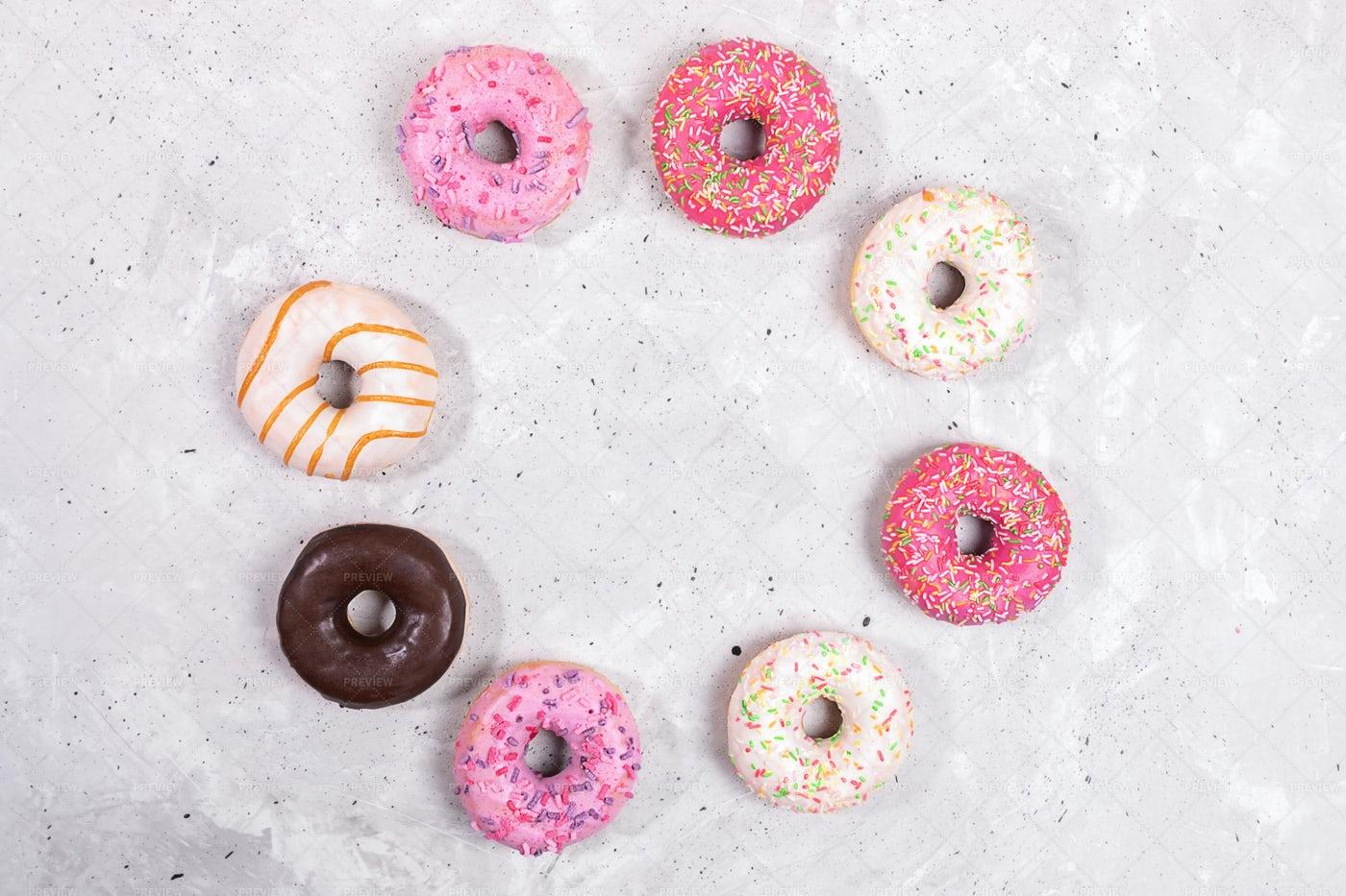 Circle Of Glazed Doughnuts On Concrete.: Stock Photos