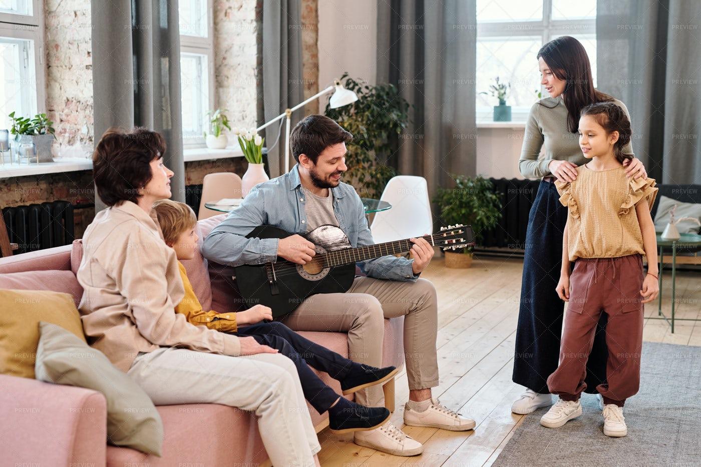 Man Playing Guitar To Family Members: Stock Photos