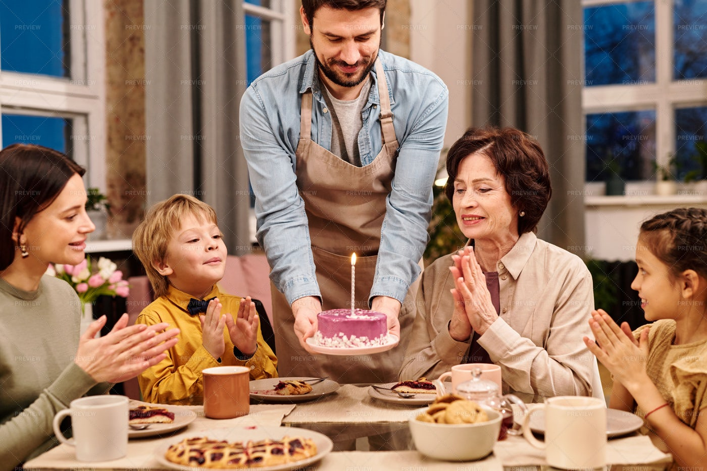 Young Man Putting Birthday Cake On Table: Stock Photos