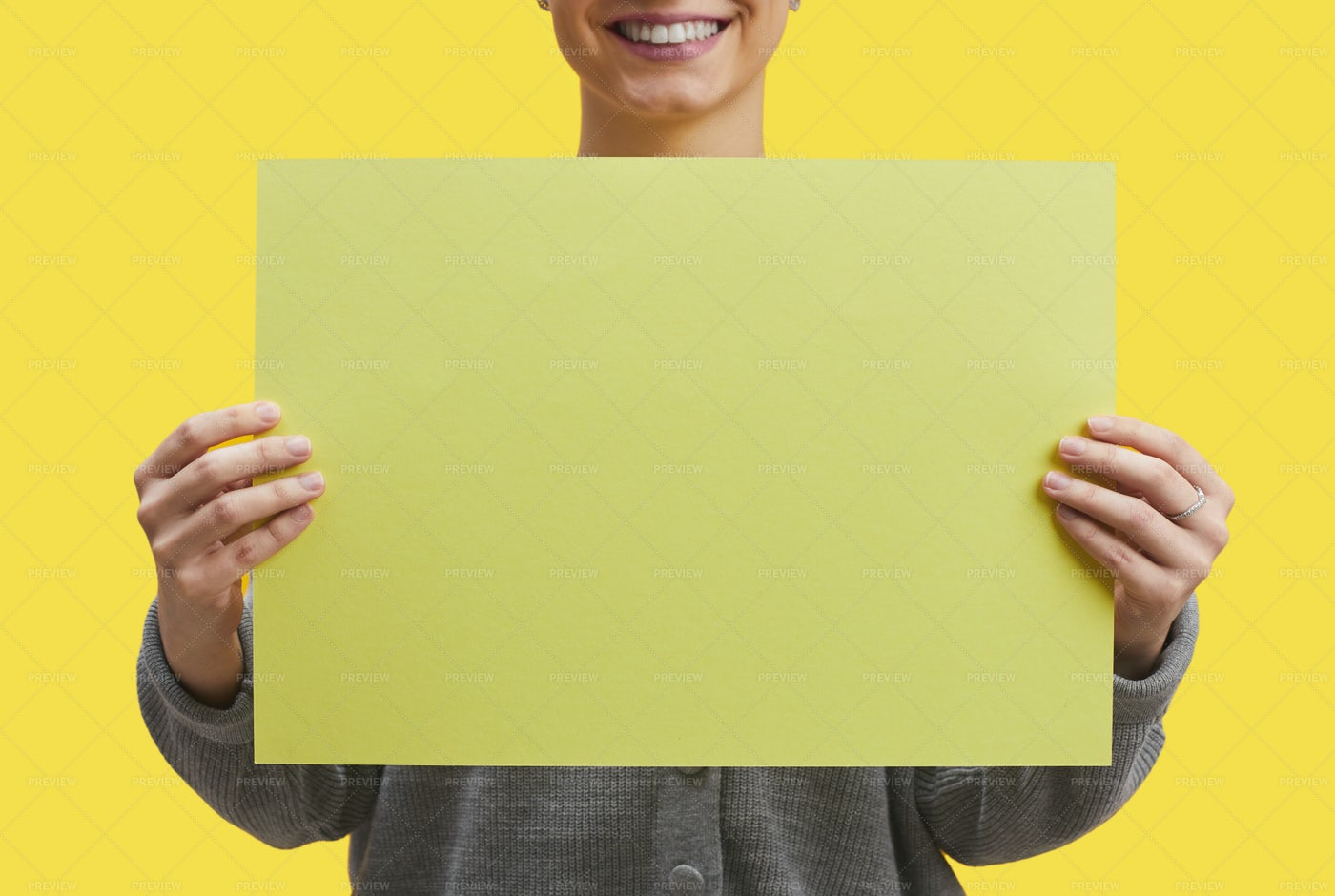 Smiling Woman Holding Sign On Yellow: Stock Photos