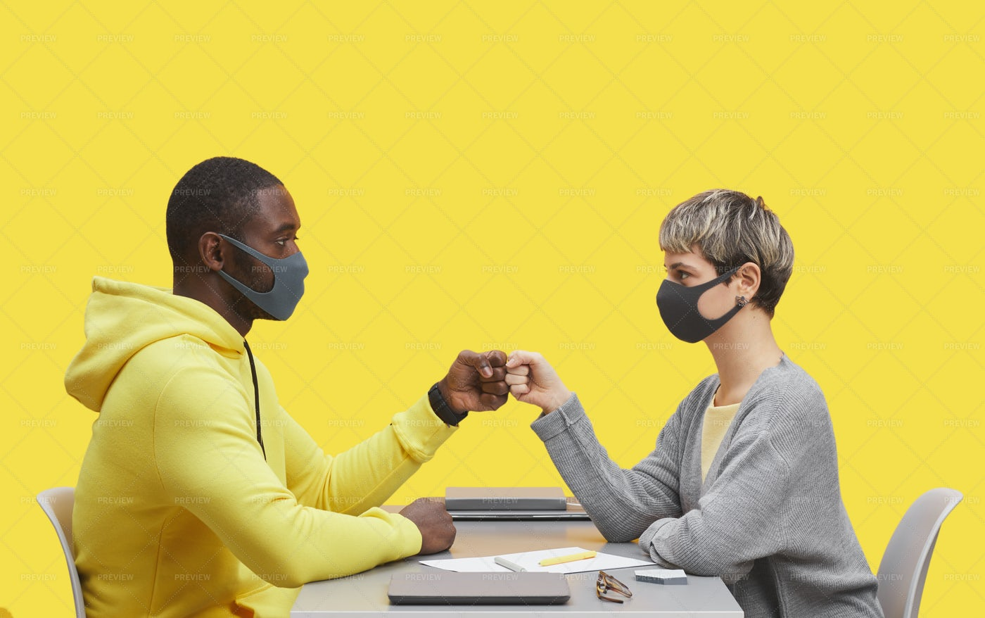 Two Colleagues Wearing Masks On Yellow: Stock Photos