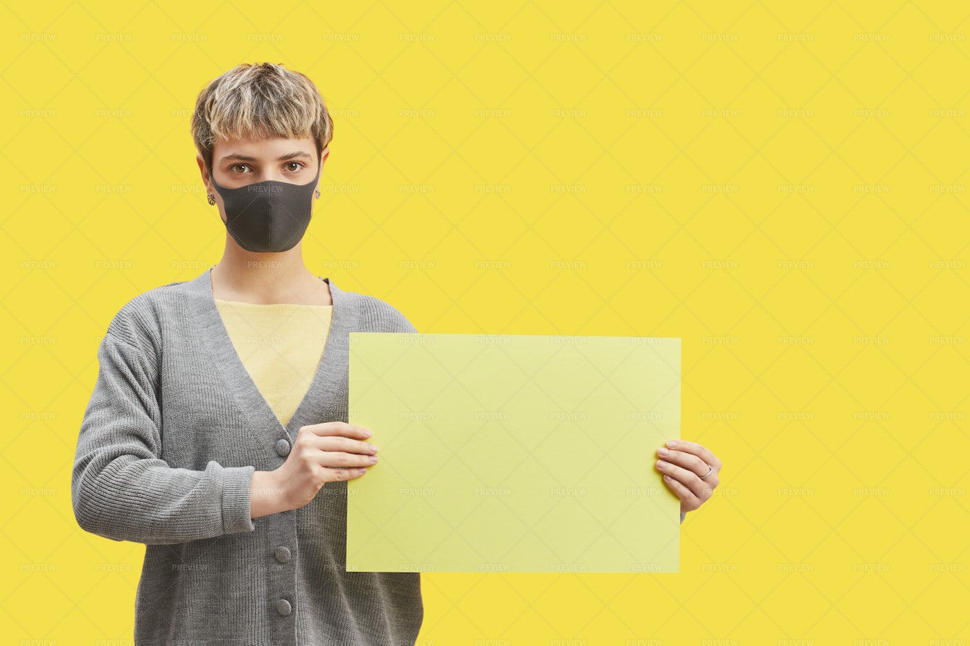Lady Wearing Mask Holding Sign On Yellow: Stock Photos
