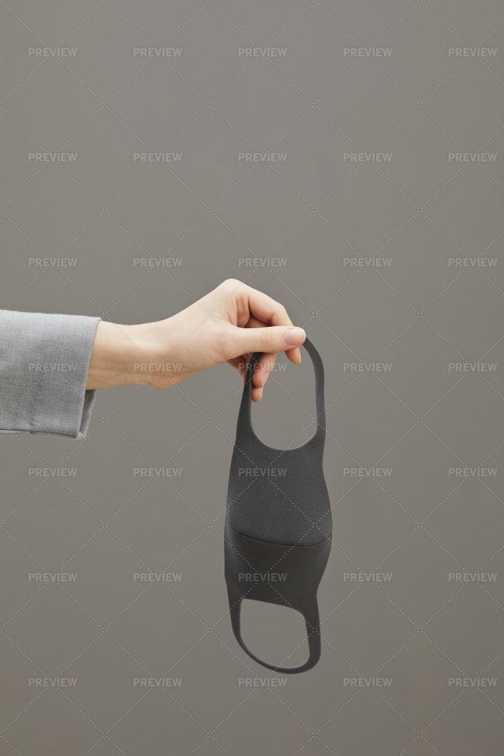 Hand Holding Mask On Grey: Stock Photos