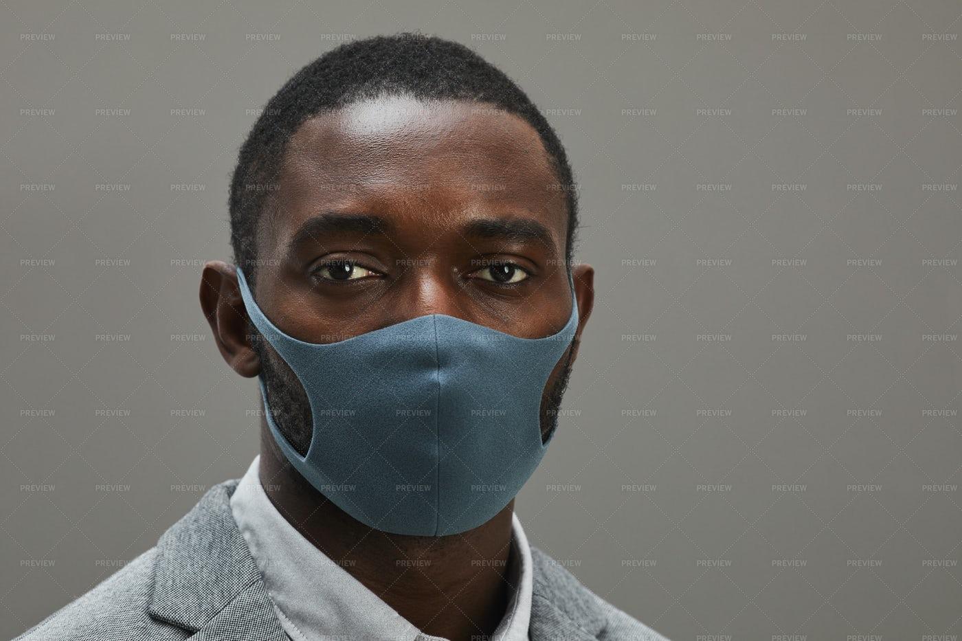 Businessman Wearing Mask On Grey: Stock Photos