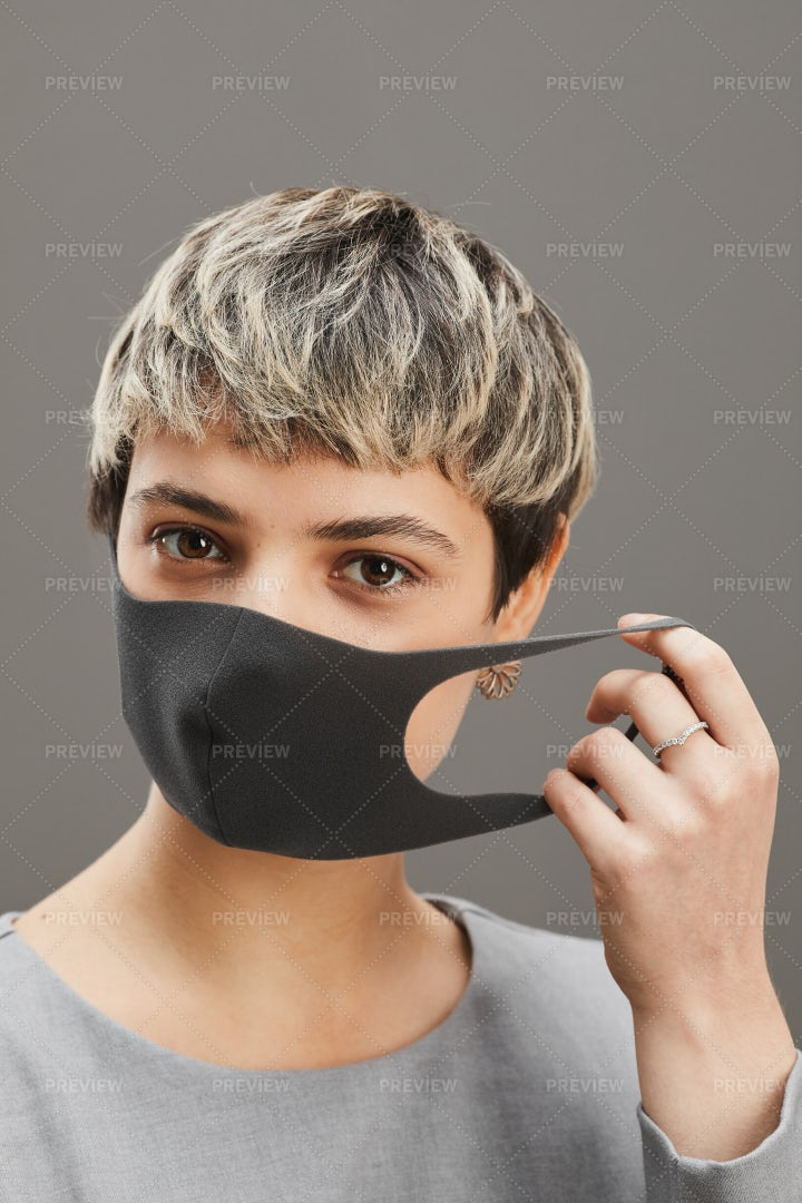 Young Woman Taking Off Mask: Stock Photos