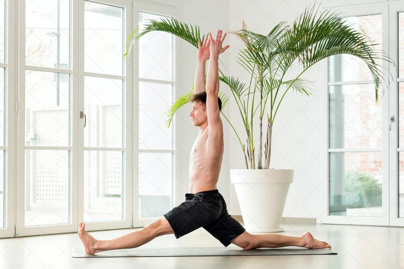 Man Performing Monkey Yoga Pose: Stock Photos