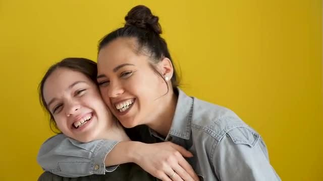 Happy Laughing Sisters On Yellow BG: Stock Video
