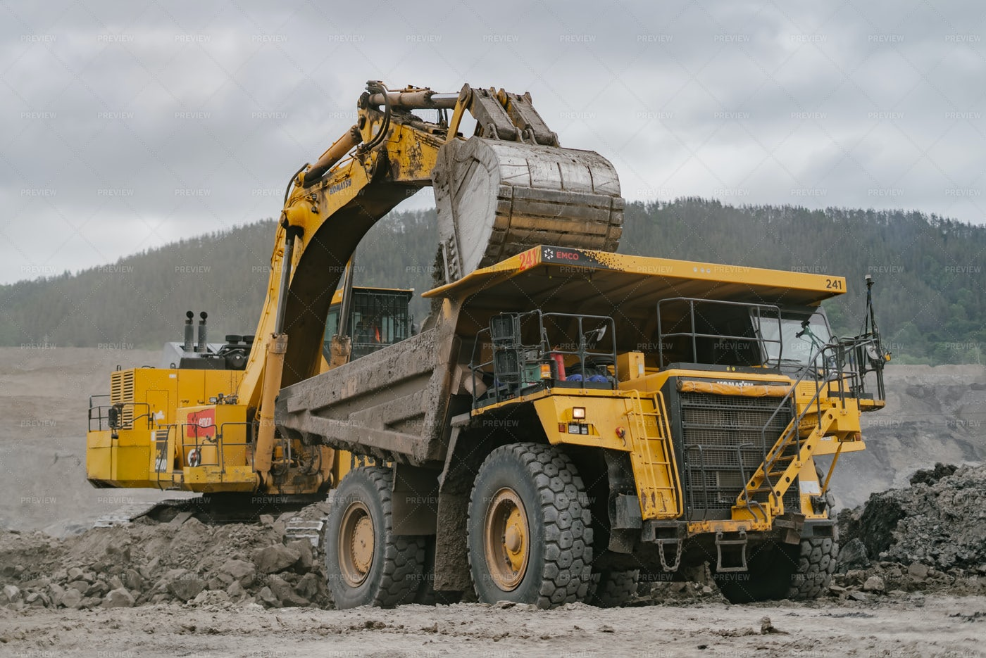 An Excavator Loads Ore Into A Dump Truck: Stock Photos