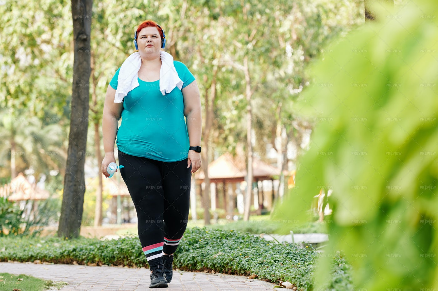 Overweight Woman Walking In Park: Stock Photos