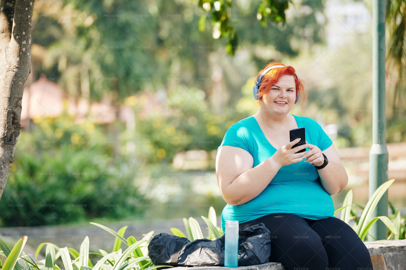 Smiling Woman Sitting In Park: Stock Photos