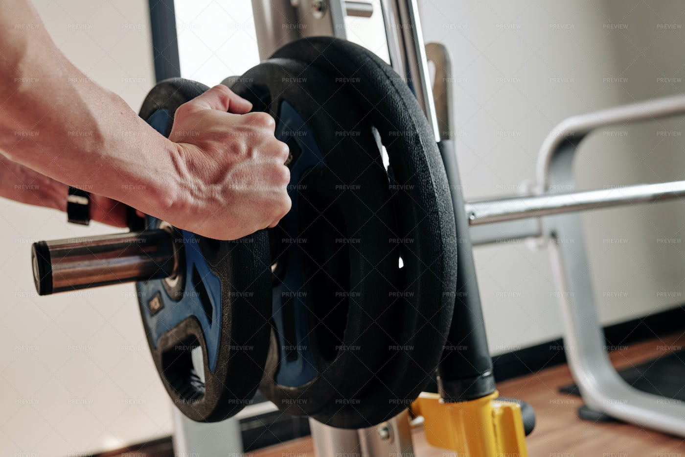 Putting Weight Plates On Barbell: Stock Photos