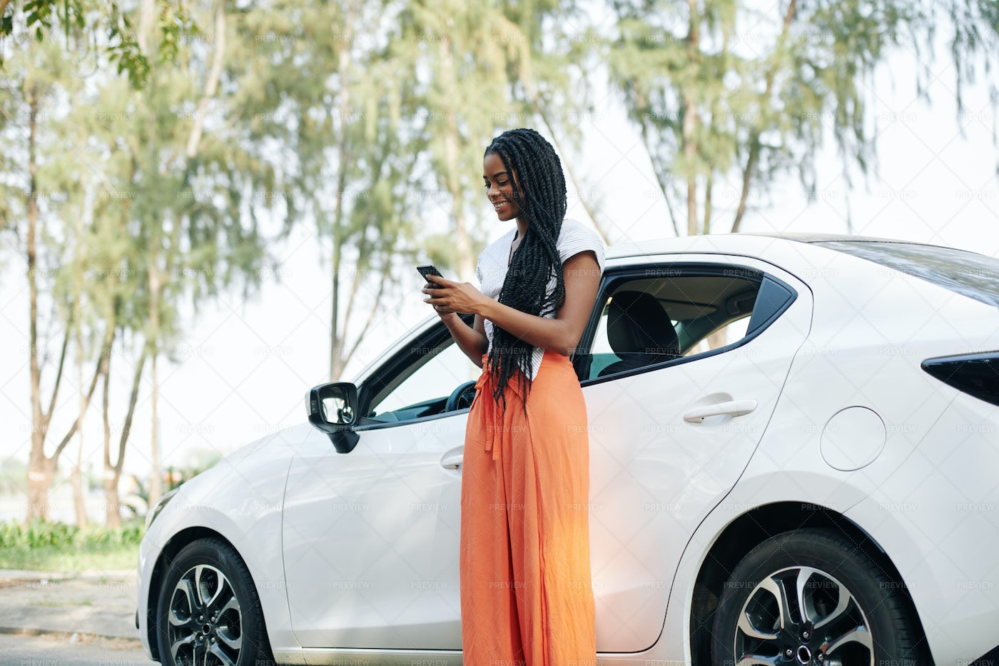 Texting In Front Of Car: Stock Photos