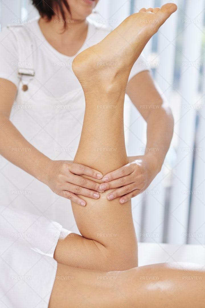 Therapist Massaging Calf Muscles: Stock Photos